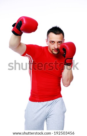 Fitness man punching with red boxing gloves isolated on white background