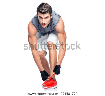 Fitness man tie shoelaces isolated on a white background. Looking at camera - stock photo