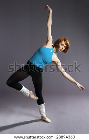 Fitness model exercising on grey background.