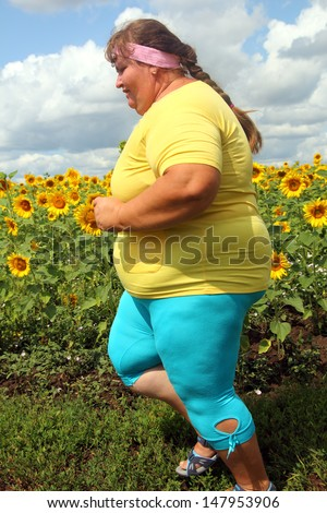 fitness - overweight woman running along field of sunflowers - stock photo