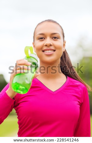 fitness, park, drink and sport concept - smiling african american woman drinking from bottle outdoors - stock photo