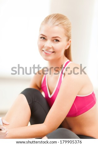 fitness, people and exercise concept - beautiful sporty woman having break in gym