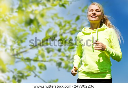 fitness, people and healthy lifestyle concept - happy young female runner jogging outdoors - stock photo