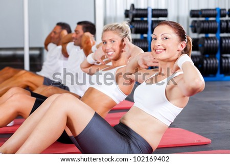 fitness people doing sit ups in gym - stock photo