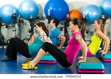 Fitness people in gym on step board; strengthening the abdominal muscles - stock photo