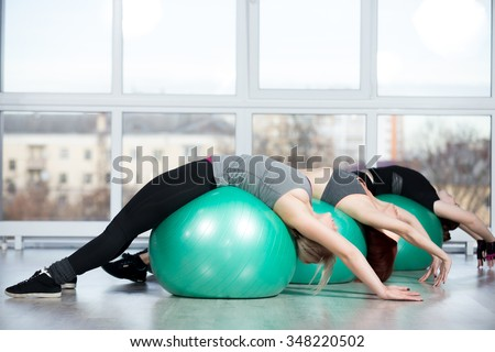 Fitness practice, group of three happy smiling beautiful fit young females working out in sports club, doing backbend exercise on green Swiss balls in class, full length - stock photo