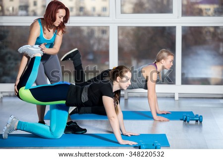 Fitness practice, group of two beautiful fit young females working out in sports club, doing kneeling kickbacks, exercise for lower back, hips and buttocks with instructor in class, full length - stock photo