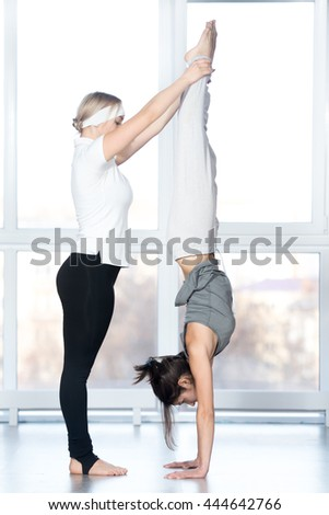 Fitness practice, instructor helping young beautiful student female to do handstand in class, Adho Mukha Vrksasana, Downward facing Tree Pose, two fit people working out in sports club, full length - stock photo