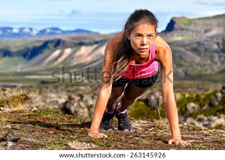 Fitness push-ups woman doing pushups outdoors in nature background. Focused female athlete showing determination and endurance exercising muscles during body core crossfit workout in summer landscape. - stock photo