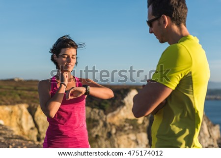 Fitness runner woman checking heart rate pulse with watch and trainer during outdoor trail running workout. Couple team outside together training for a marathon or decathlon competition.