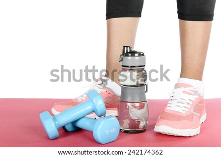 Fitness running shoes with a water bottle and dumbbells on a pink floor. - stock photo