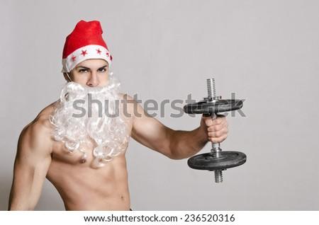 Fitness Santa in studio shot lifting weights - stock photo