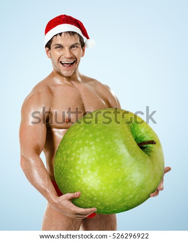 fitness sexy Santa Claus on blue background, hold great green apple and laughing