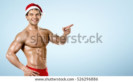 fitness sexy Santa Claus , show index finger and smile, on blue background