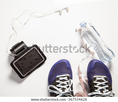 fitness shoes with measuring tape water and earphones healthy lifestyle - stock photo