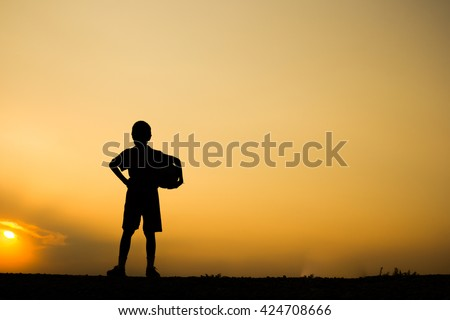 Fitness silhouette sunrise A boy holding soccer ball after play, workout wellness concept. - stock photo