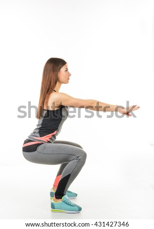 Fitness smiling woman in the form of the squat with arms outstretched.Healthy lifestyle
