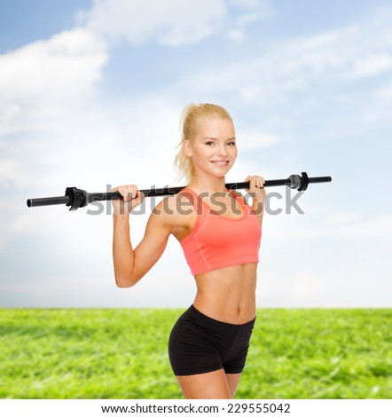 fitness, sport and exercise concept - smiling sporty woman exercising with barbell