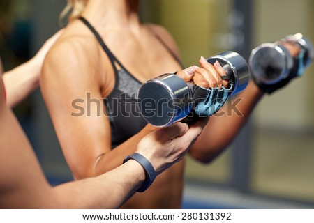 fitness, sport, bodybuilding and weightlifting concept - close up of young woman and personal trainer with dumbbells flexing muscles in gym - stock photo
