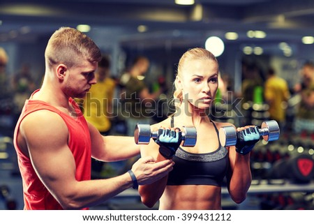 fitness, sport, bodybuilding and weightlifting concept - young woman and personal trainer with dumbbells flexing muscles in gym - stock photo