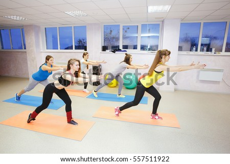 fitness, sport, dance and lifestyle concept - group of smiling girls with coach dancing zumba in gym or studio.