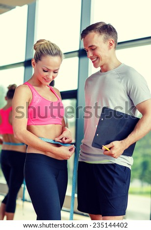 fitness, sport, exercising and diet concept - smiling young woman with measuring tape and personal trainer in gym - stock photo
