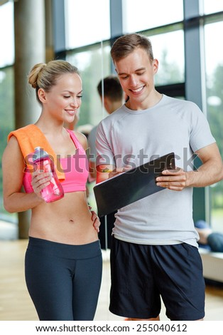 fitness, sport, exercising and diet concept - smiling young woman with personal trainer after training in gym - stock photo