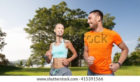 fitness, sport, exercising and healthy lifestyle concept - smiling couple running or jogging over summer park background - stock photo