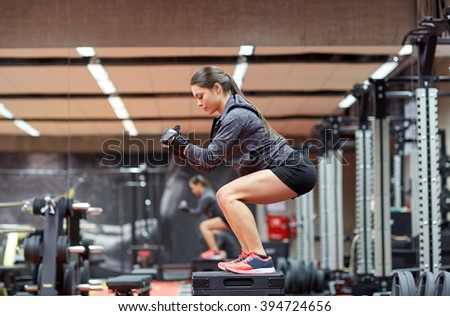 fitness, sport, exercising and people concept - woman doing squats on platform in gym - stock photo