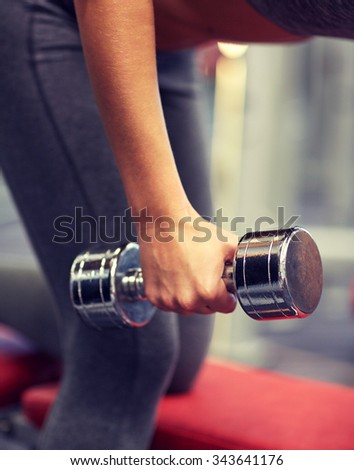 fitness, sport, exercising and weightlifting concept - close up of young woman and personal trainer with dumbbells flexing muscles in gym - stock photo