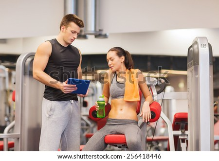 fitness, sport, exercising, technology and people concept - smiling young woman and personal trainer with tablet pc computer in gym - stock photo
