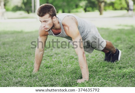 fitness, sport, exercising, training and lifestyle concept - young man doing push ups or plank exercise on grass in summer park - stock photo