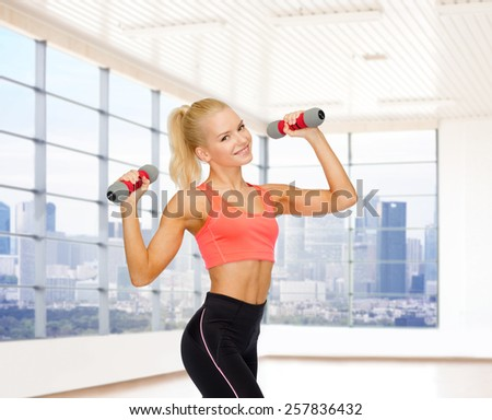 fitness, sport, fitness and people concept - smiling woman with light weight dumbbells flexing biceps over gym or home background