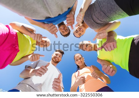 fitness, sport, friendship and healthy lifestyle concept - group of happy teenage friends in circle outdoors showing thumbs up - stock photo