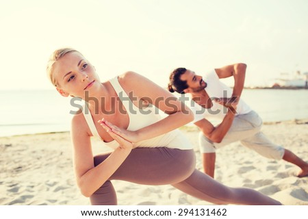 fitness, sport, friendship and lifestyle concept - close up of couple making yoga exercises on beach - stock photo