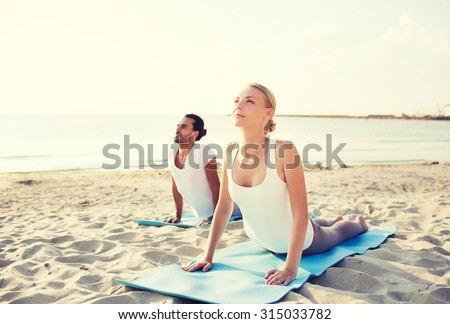 fitness, sport, friendship and lifestyle concept - couple making yoga exercises lying on mats outdoors - stock photo