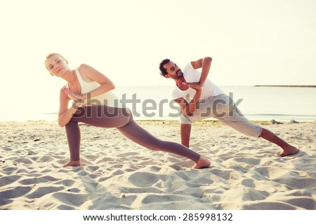 fitness, sport, friendship and lifestyle concept - couple making yoga exercises on beach - stock photo
