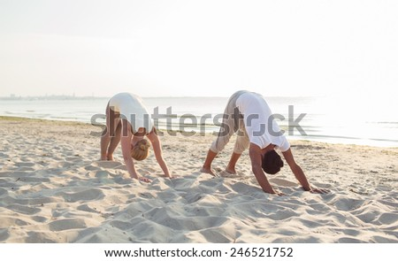 fitness, sport, friendship and lifestyle concept - couple making yoga exercises on sand outdoors - stock photo
