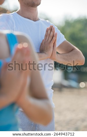 Fitness, sport, friendship and lifestyle concept - smiling couple making meditation yoga exercises on beach at morning