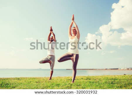 fitness, sport, friendship and lifestyle concept - smiling couple making yoga exercises outdoors - stock photo