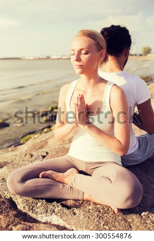 fitness, sport, friendship and lifestyle concept - smiling couple making yoga exercises sitting outdoors - stock photo