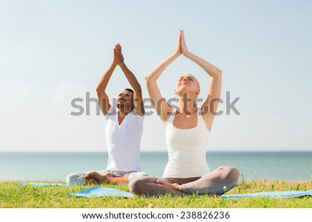 fitness, sport, friendship and lifestyle concept - smiling couple making yoga exercises sitting on mats outdoors - stock photo