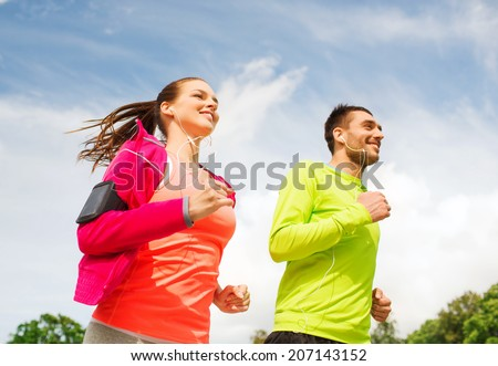 fitness, sport, friendship and lifestyle concept - smiling couple with earphones running outdoors - stock photo