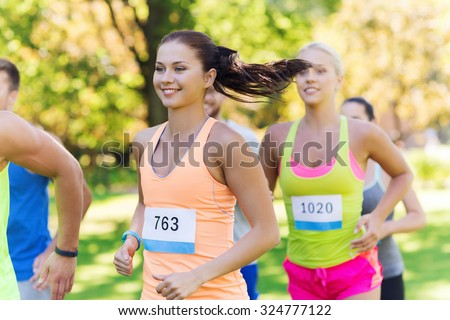 fitness, sport, friendship, race and healthy lifestyle concept - group of happy teenage friends or sportsmen running marathon with badge numbers outdoors - stock photo