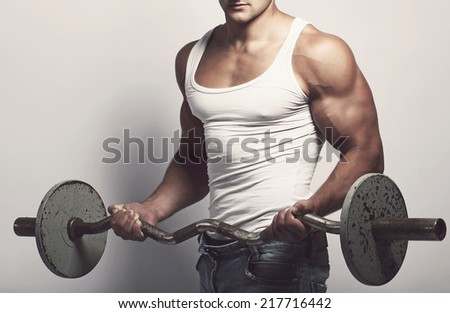 Fitness, sport. Handsome guy with barbell