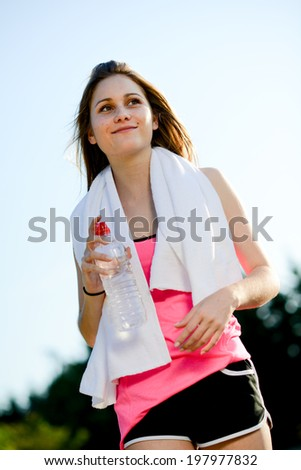 fitness sport healthy cheerful young woman running outdoor in the countryside and drinking water - stock photo