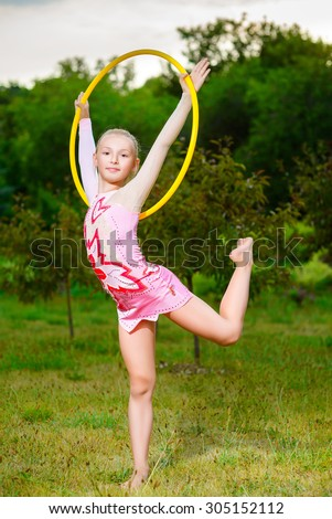 fitness, sport, people and healthcare concept - little sporty girl exercising with hula hoop over park background