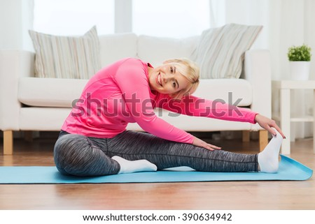 fitness, sport, people and healthy lifestyle concept - happy plus size woman stretching leg on mat at home - stock photo