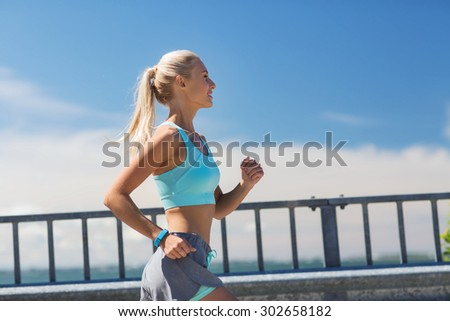 fitness, sport, people and healthy lifestyle concept - smiling young woman with heart rate watch running outdoors - stock photo