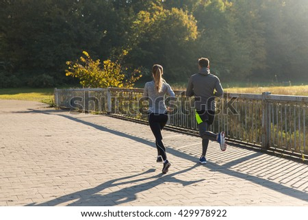 fitness, sport, people and jogging concept - couple running outdoors - stock photo